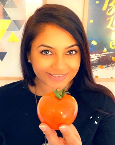 Photo of Pooja Adhyaru holding a tomato